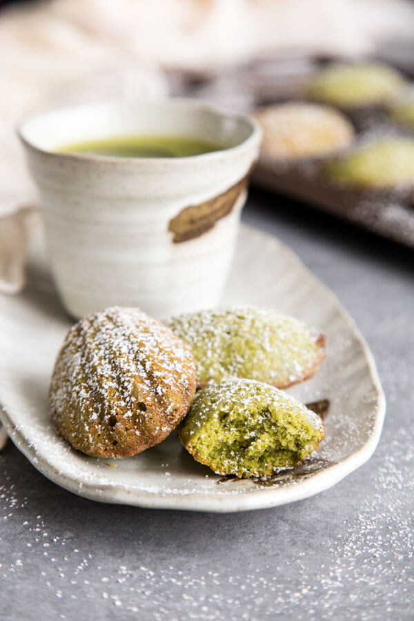 Matcha madeleines on a plate with a cup of tea