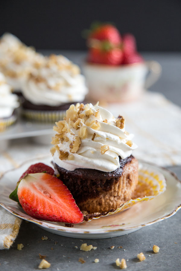 A banana split cupcake on a plate with the cupcake paper torn off to show the chocolate and strawberry cake layers