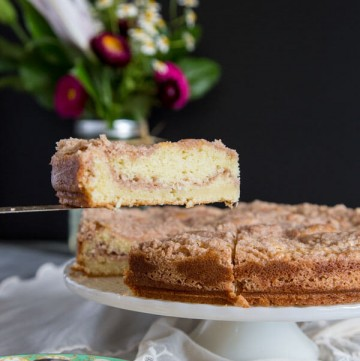 A slice of buttermilk coffee cake is lifted from the cake stand