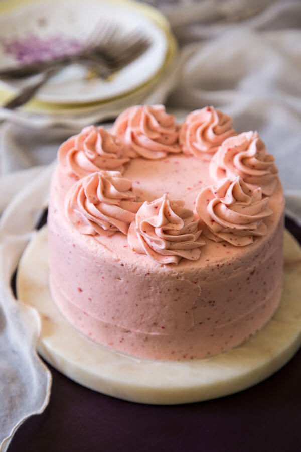 Strawberry cake with strawberry cream cheese frosting on a cake stand