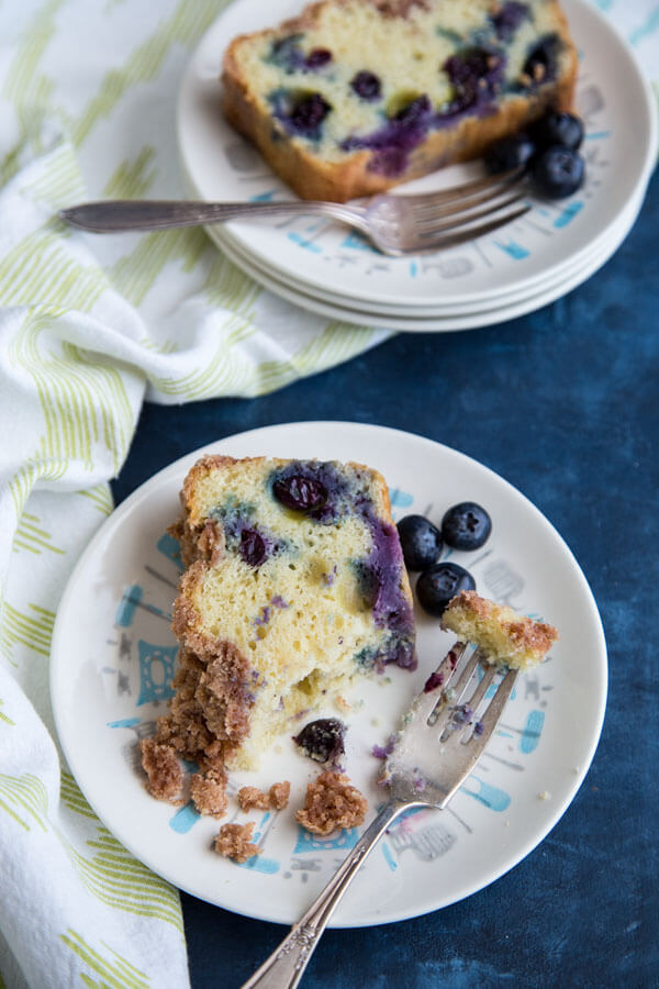 A slice of eaten blueberry coffee cake on a plate