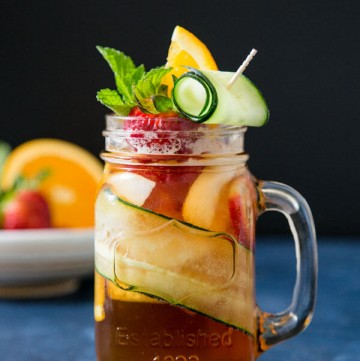 A glass of Pimm's cup cocktail garnished with cucumber, strawberry and orange slice on a blue table top
