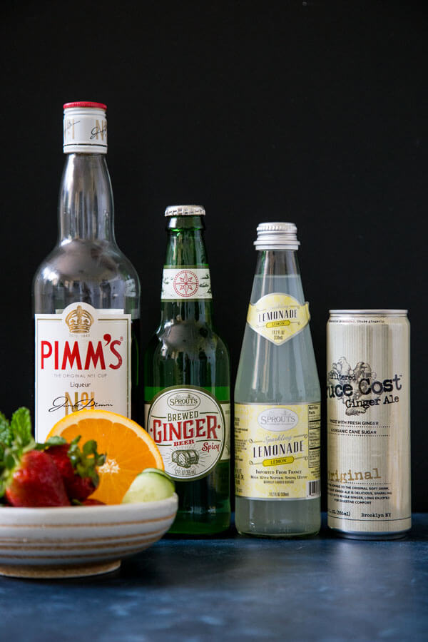 Bottled ingredient for Pimm's cup: Pimm's No. 1, ginger beer, sparkling lemonade, ginger ale, next to a bowl of fruit garnishing