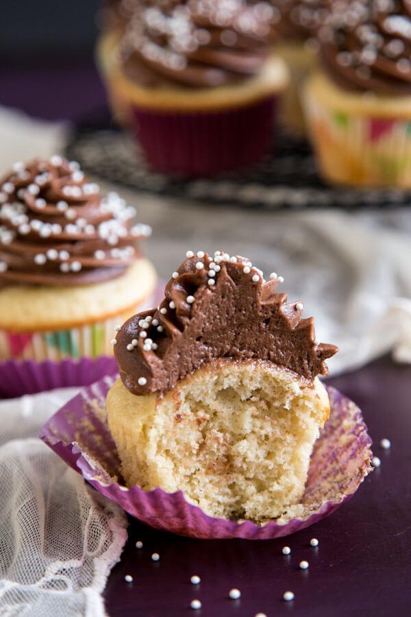 Half eaten vanilla cupcake with chocolate frosting