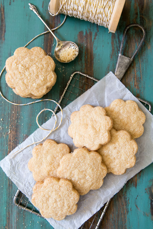 Caramelized sugar shortbread cookies piled on a piece of parchment paper