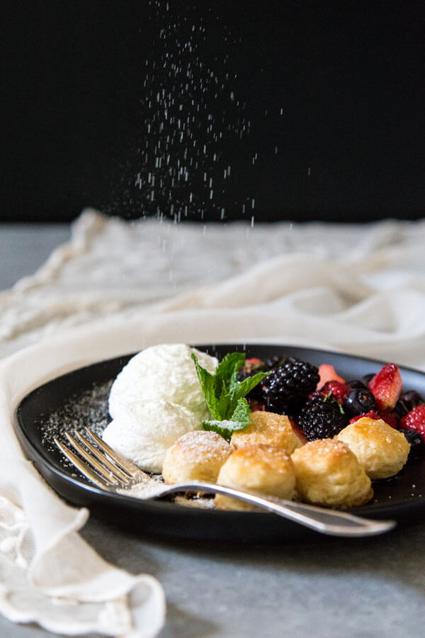 Deconstructed berries and cream shortcake on a plate being sprinkled with caramel dust