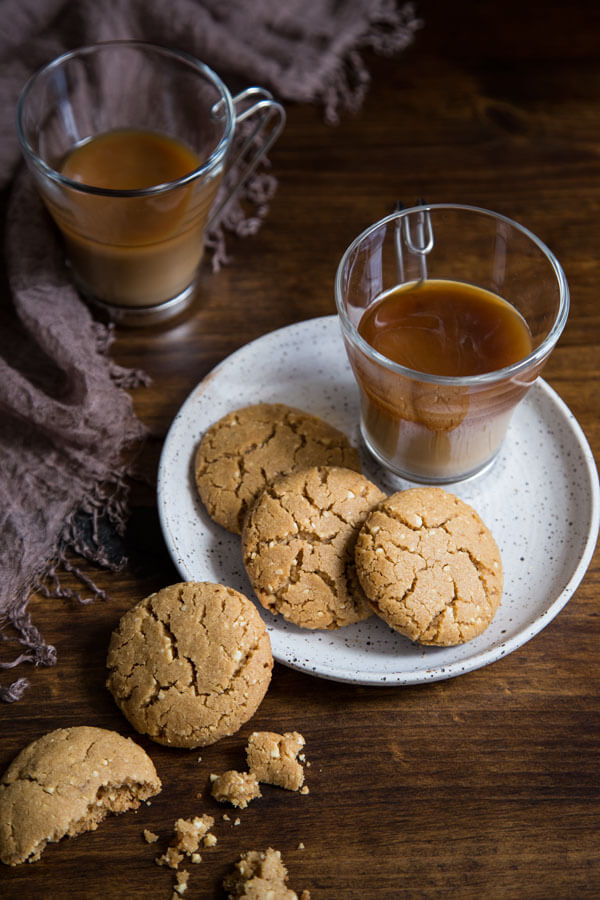 Brown butter peanut butter cookies on a plate with two glasses of coffee
