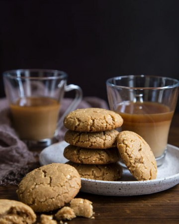 A stack of brown sugar peanut butter cookies on a plate with two glasses of coffee