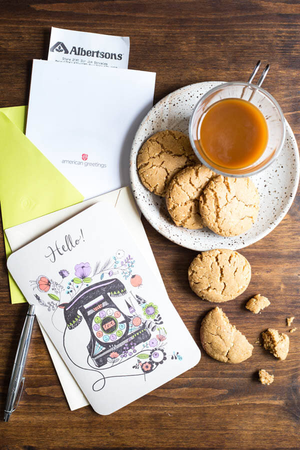 Peanut butter cookies on a plate with a glass of coffee next to two American Greetings cards