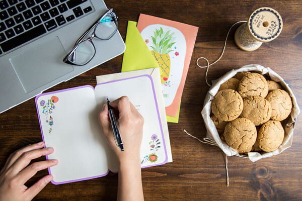 Peanut cookies in a tin on a table top with a person writing in a greeting card