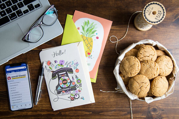 A tin of peanut butter cookies with brown sugar on a table top next to some greeting cards, a pen, a phone, a laptop with a pair of glasses on top