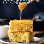 A stack cornbread being drizzled with honey.