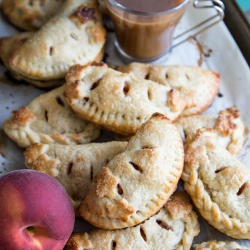 A pile of peach hand pies on a baking sheet