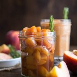 Peach compote in a glass jar with a rosemary sprig