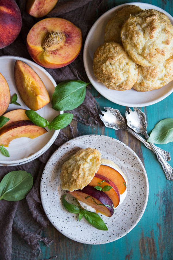 Peach shortcake being assembled with whipped cream and macerated peach slices on a plate with basil leaves