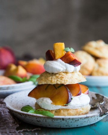 Fresh peach shortcake on a plate with basil leaves