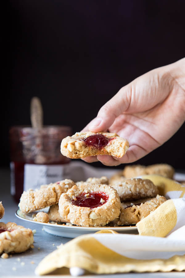 Picking up a jam thumbprint cookie from a plate