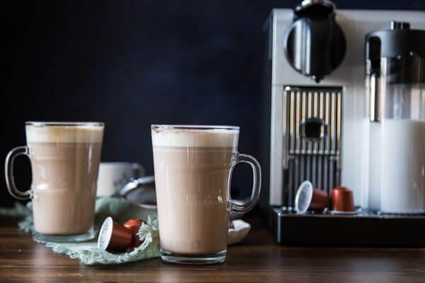 Two tall mugs of chocolate hazelnut latte next to a Nespresso machine