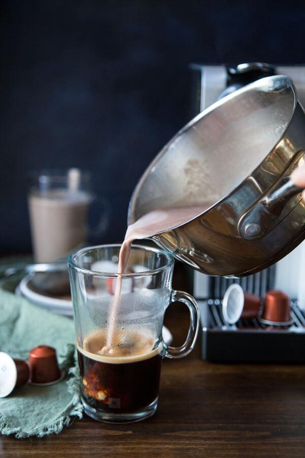 Pouring hazelnut hot chocolate mixture into a coffee mug