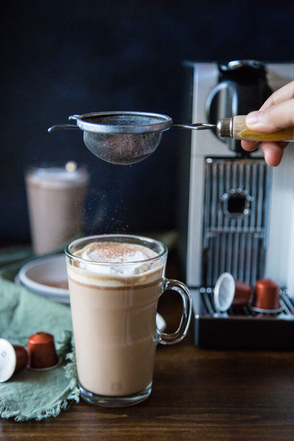Adding cocoa powder to a mug of chocolate hazelnut latte