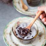 Che dau den with coconut milk in a small bowl