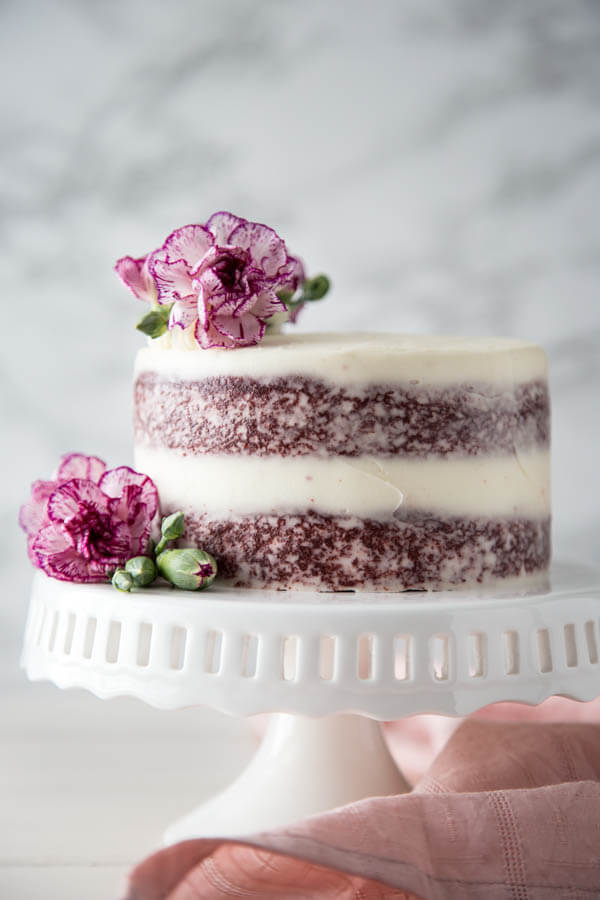 A mini red velvet cake on a cake stand