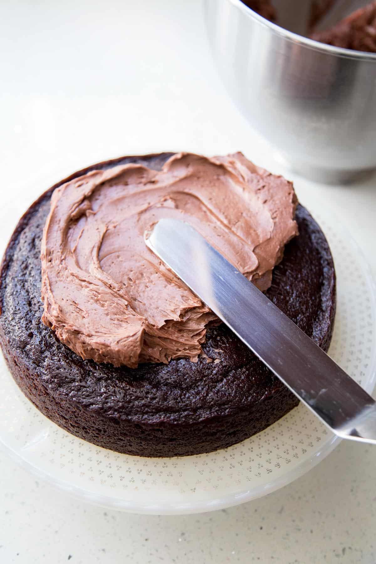 Adding chocolate buttercream on chocolate cake