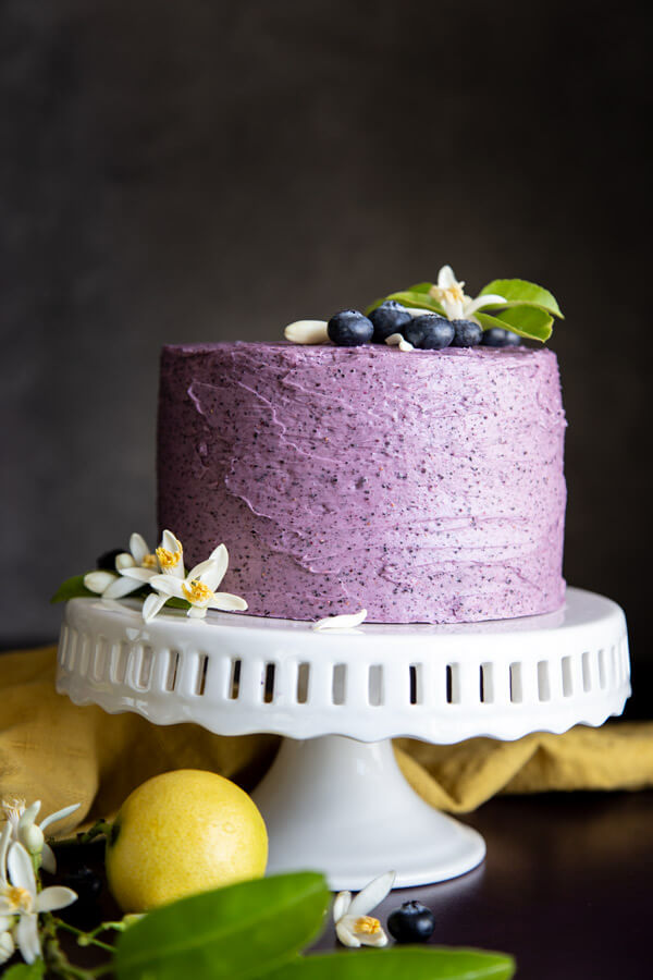 Lemon blueberry cake on a white cake stand