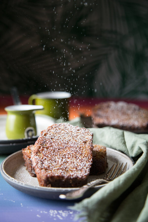 Powdered sugar falling on banana bread french toast on a plate