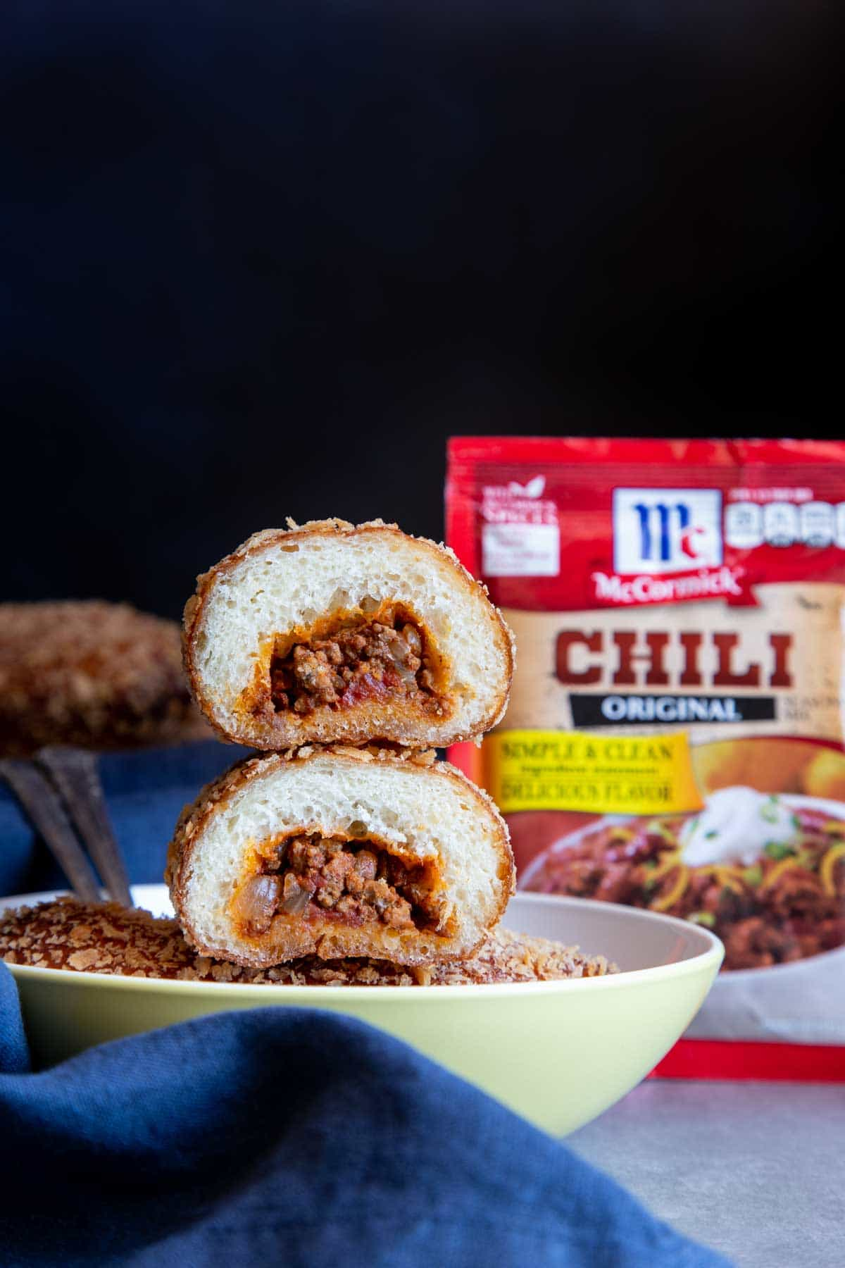 A stack of beef chili bread cut in half with the filling exposed in a bowl