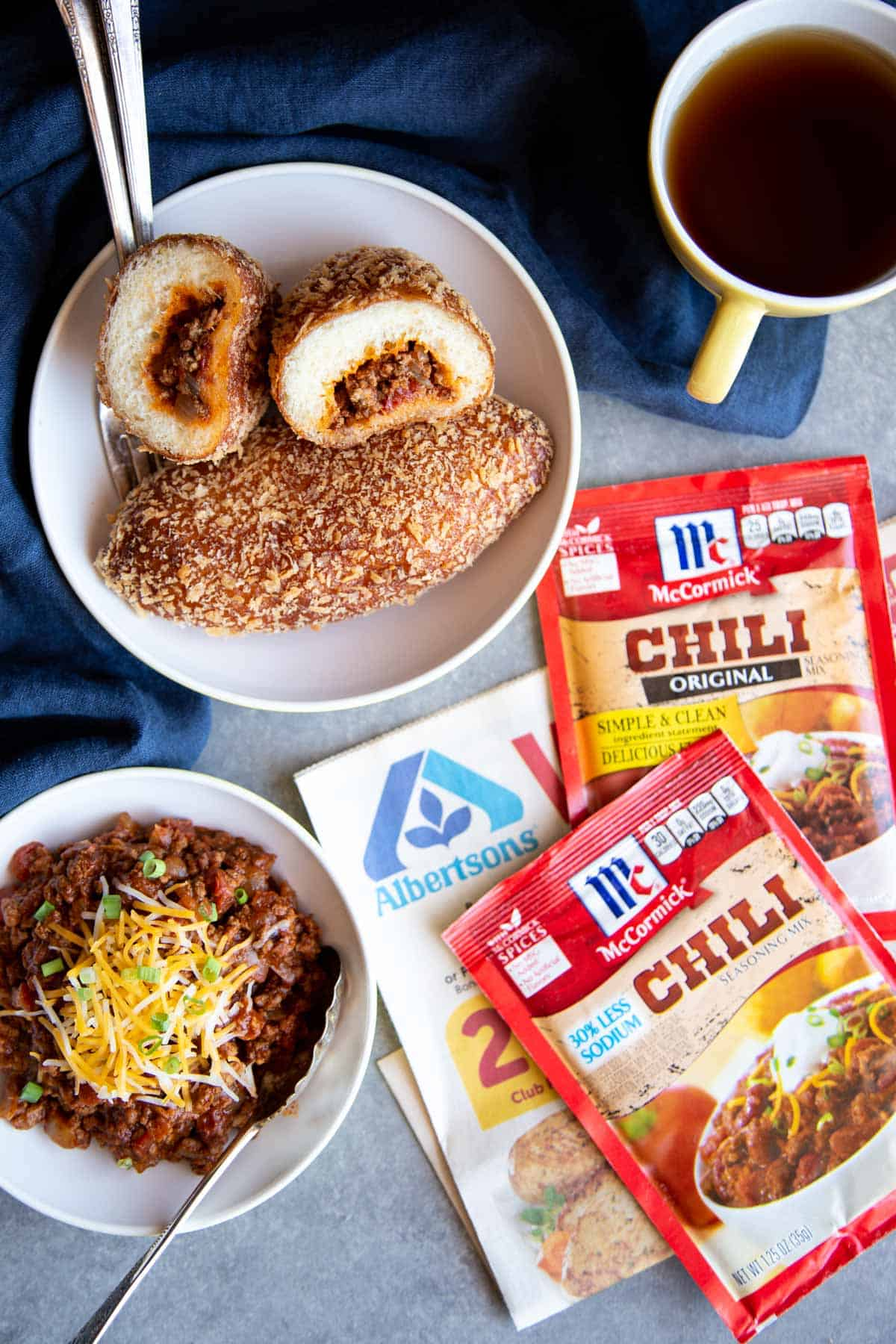 Chili bread in a bowl next to a bowl of chili and a cup of black tea