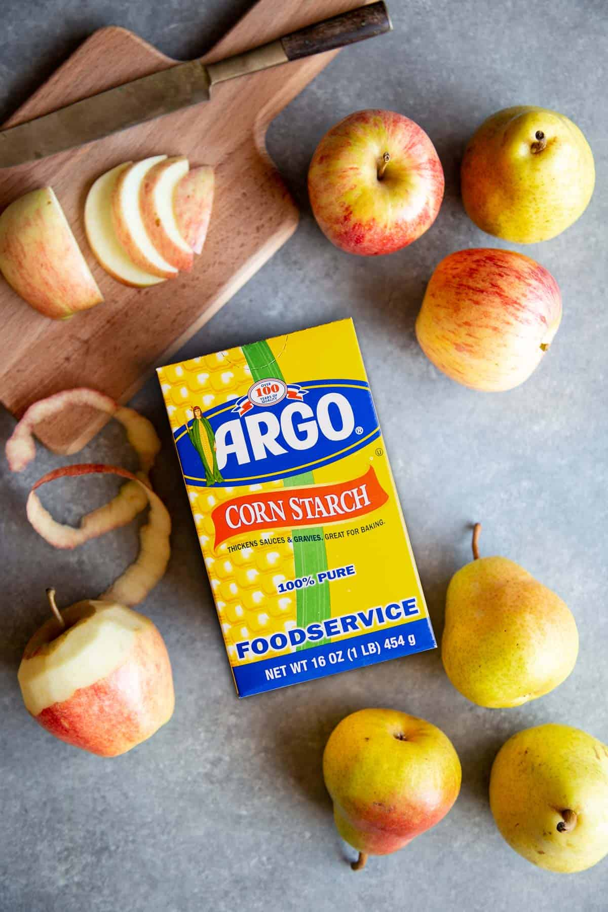 A box of Argo cornstarch on a board with apples and pears