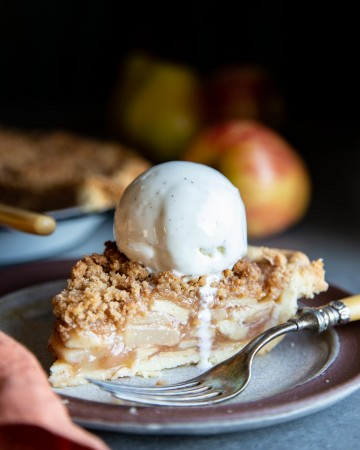 A slice of apple pear pie with a scoop of ice cream on top