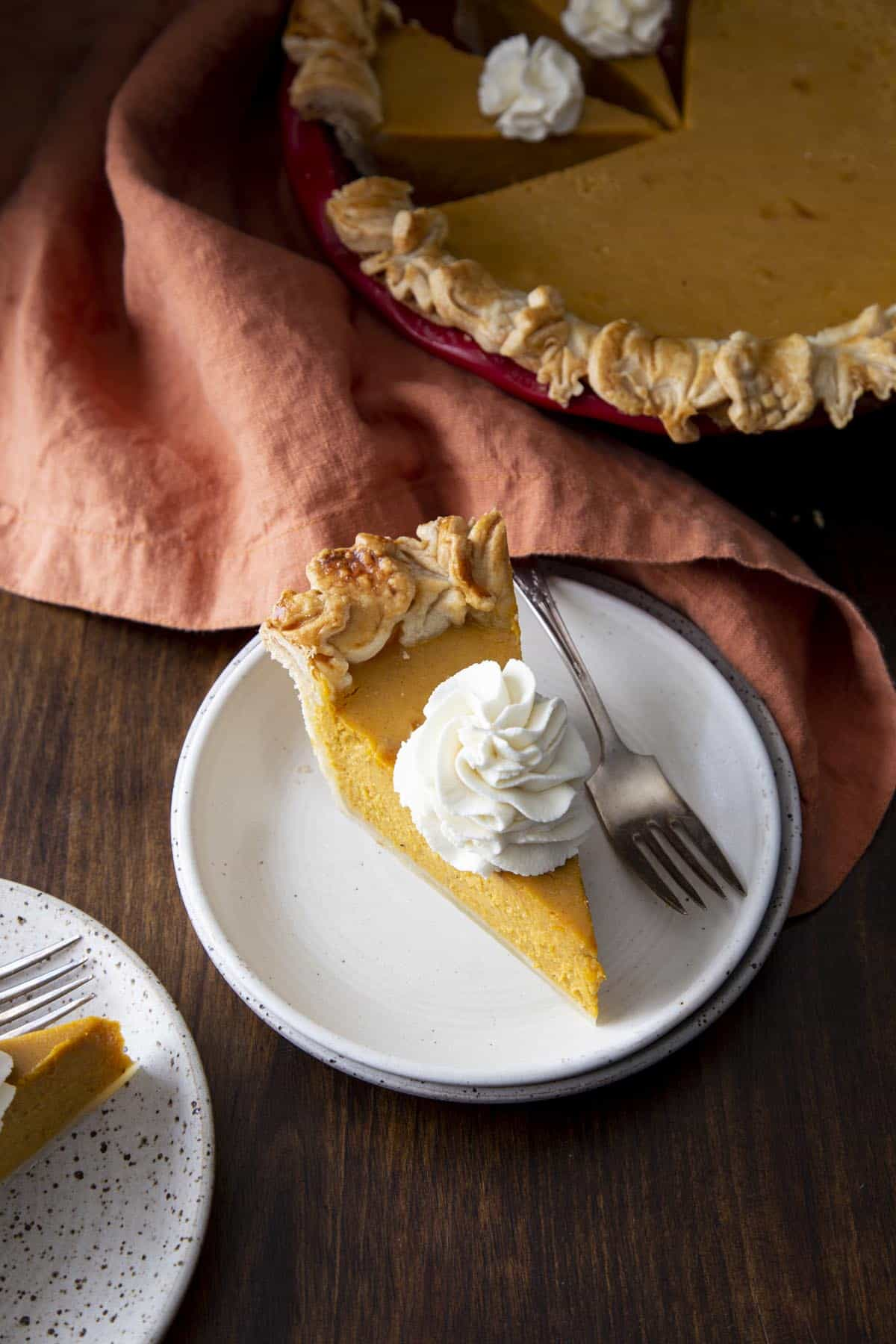 A slice of pumpkin pie with whipped cream on a white plate next to a fork