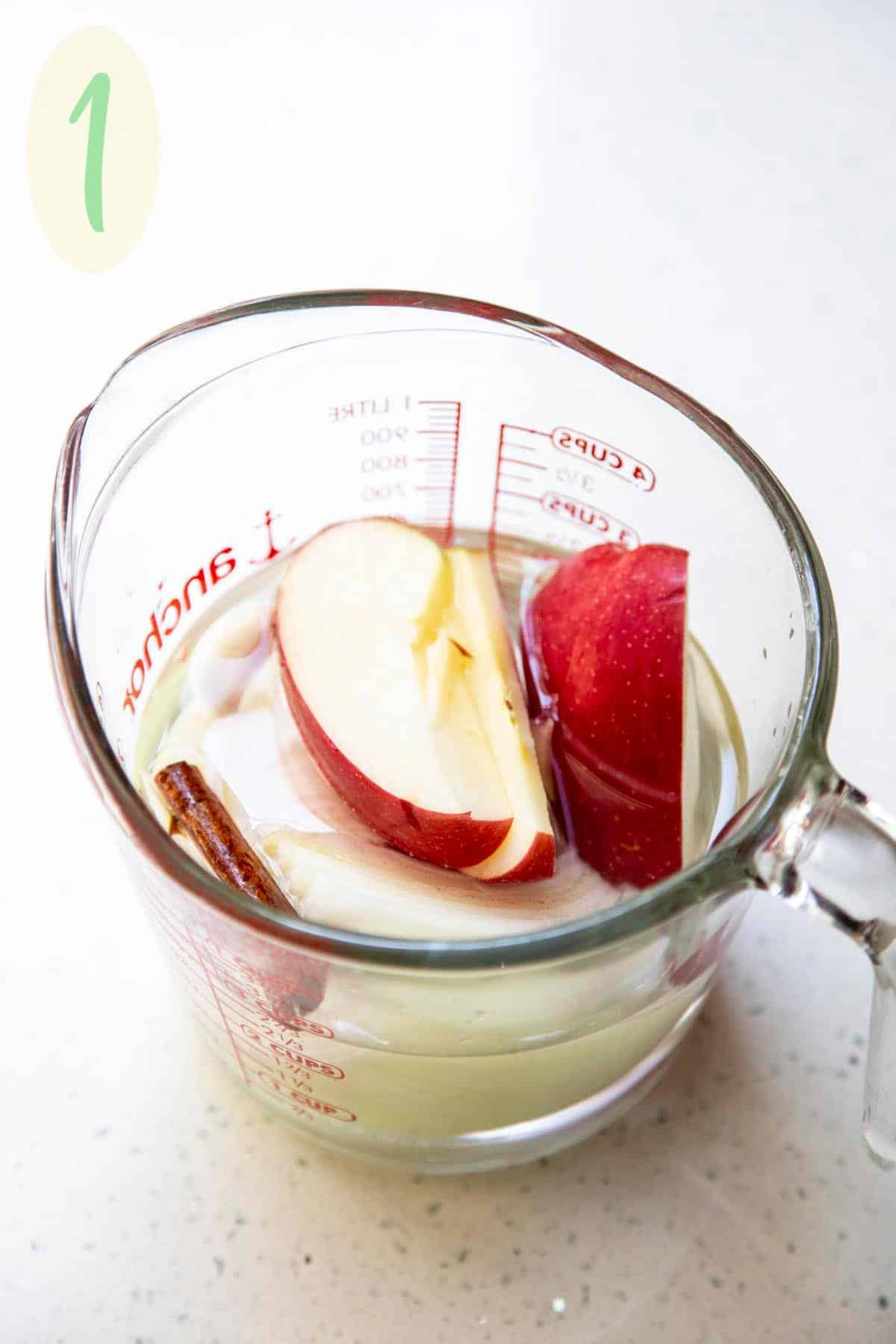 Apple, onion, cinnamon, garlic in water in a pyrex measuring cup