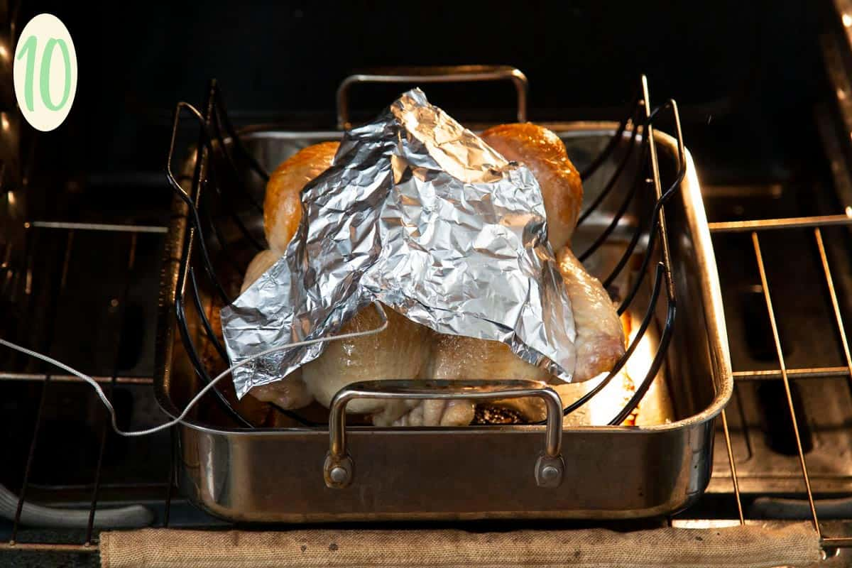 Turkey in a roasting pan in the oven with a piece of foil over it