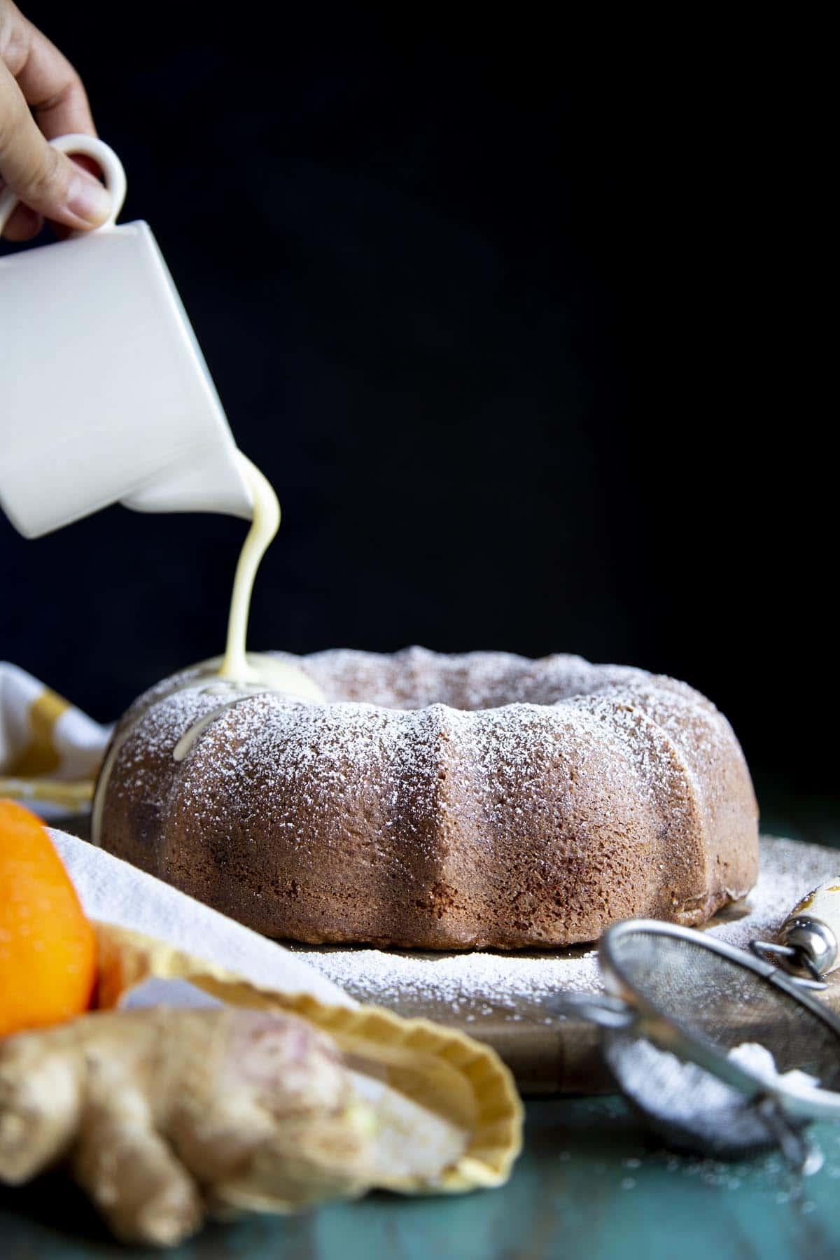 Orange glaze is being poured on top of a gingerbread bundt cake