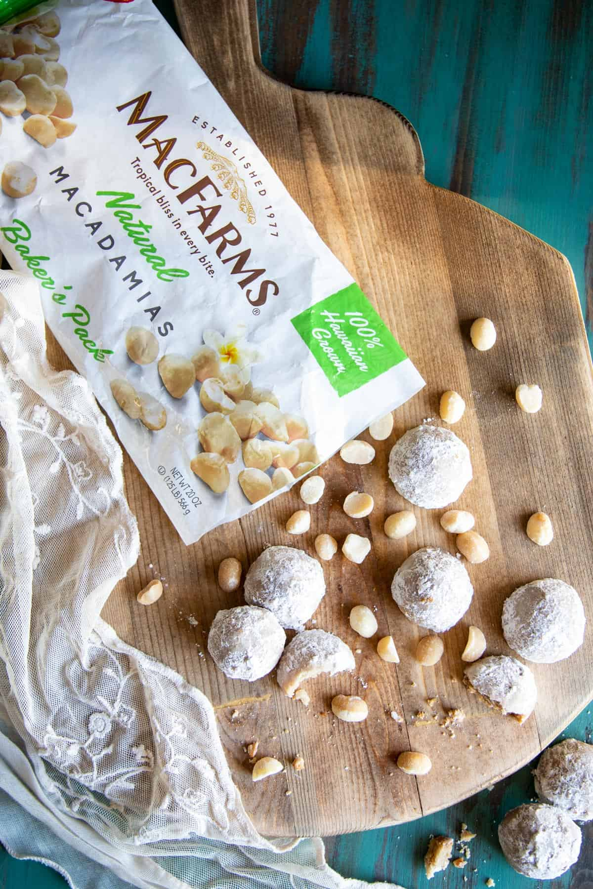 Snowball cookies and macadamia nuts on a wooden board