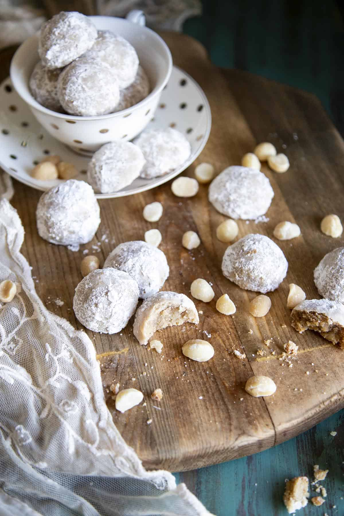 Snowball cookies spread on a wooden board with macadamia nuts