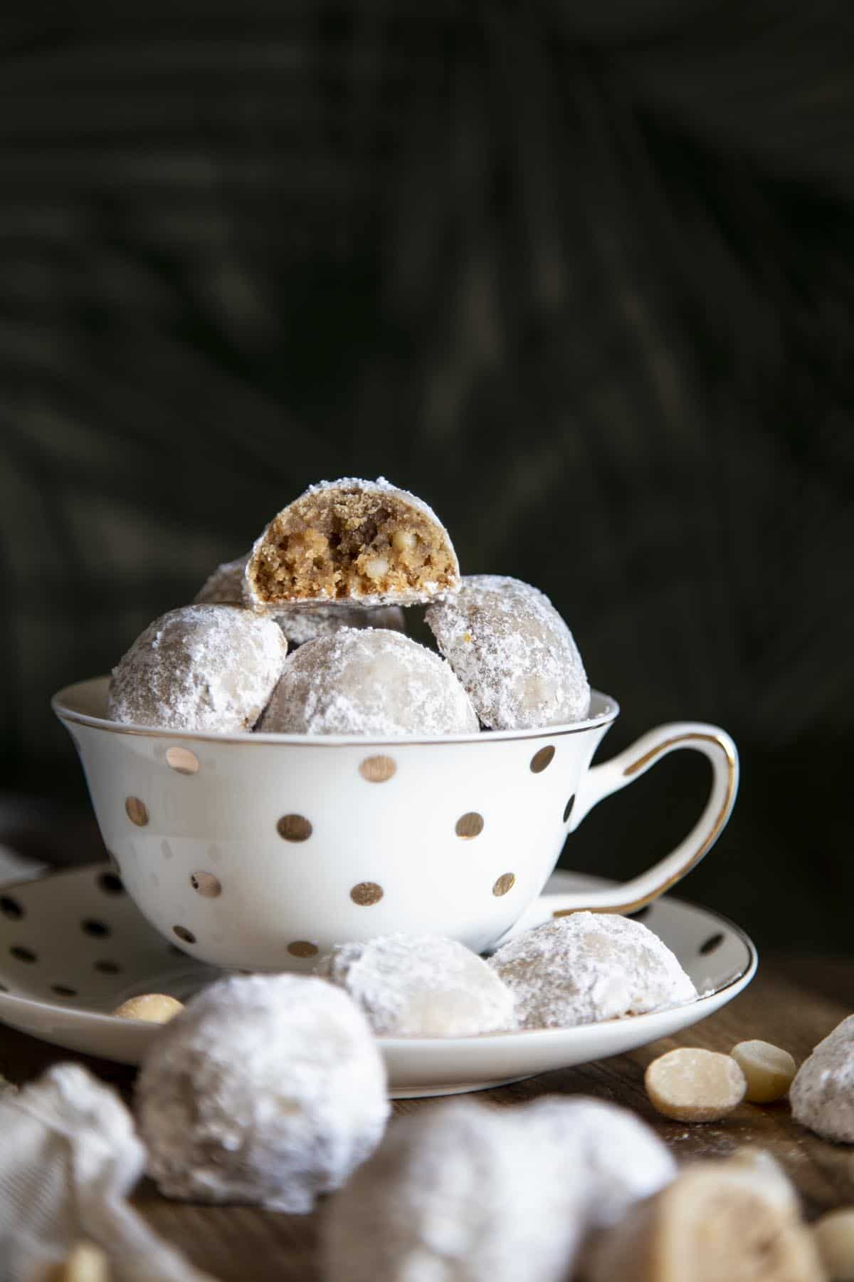 Snowball cookies in a tea cup with one half eaten cookie at top