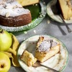 A slice of almond pear cake on a plate with a fork