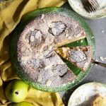 Arial view of a pear cake on a green platter with a slice being served