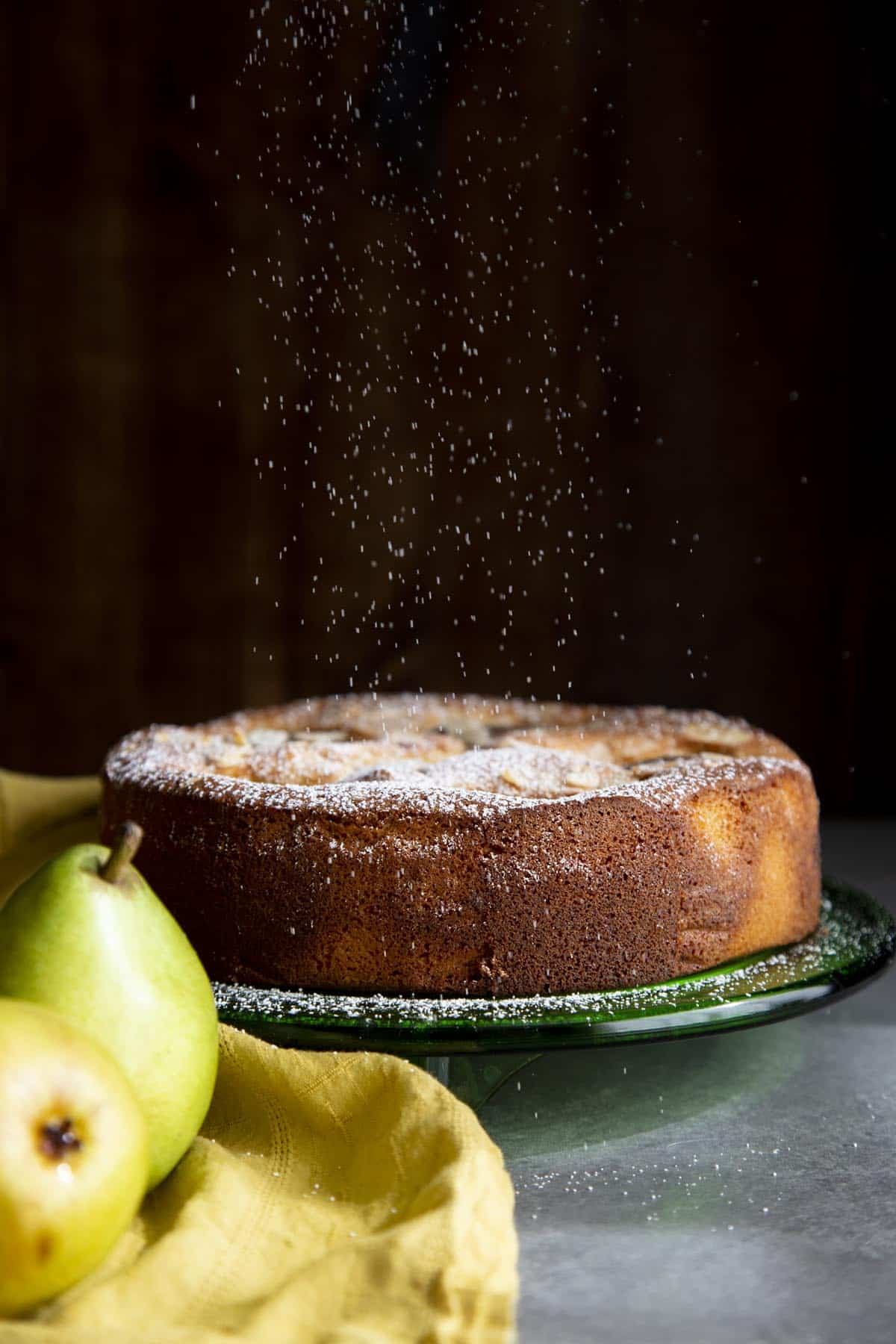 A pear almond cake on a green cake plate with powdered sugar raining down on it
