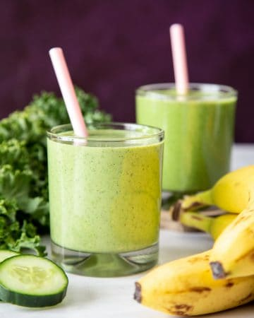 Green smoothie in 2 glasses with pink straws next to banana, kale and cucumber slice.