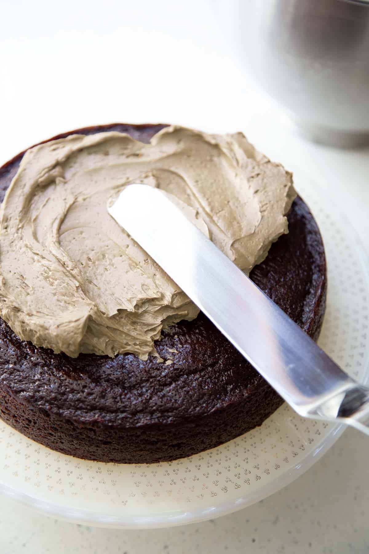 Frosting is being spread on a layer of chocolate cake