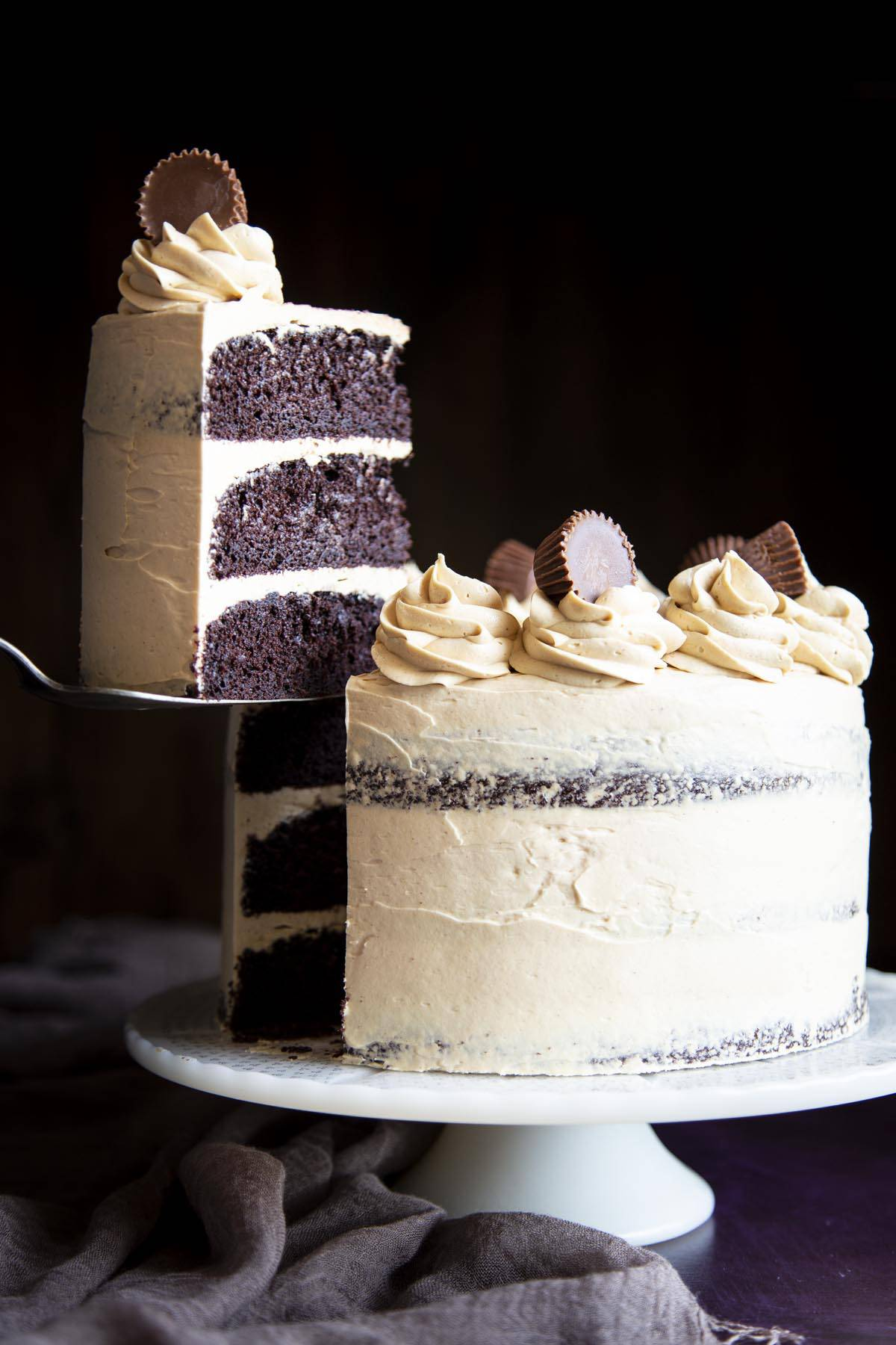 A slice of chocolate cake covered in peanut butter frosting is being lifted off the cake stand with the whole cake