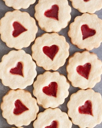 Stained glass cookies with heart shaped candy in the middles laying flat on a grey surface