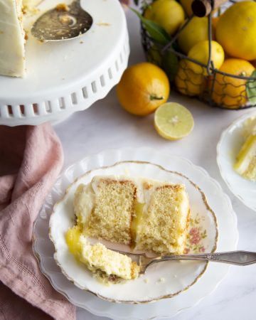 A slice of lemon cake on a plate, a bite is taken off and on a fork