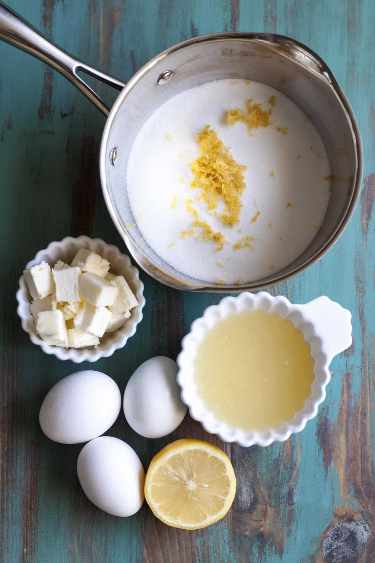 Ingredients for lemon curd on a green surface