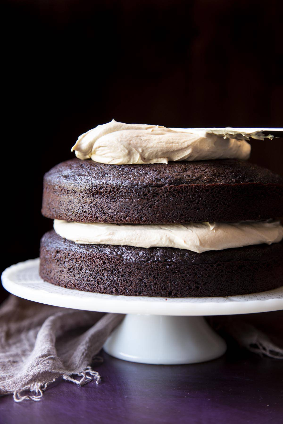 Peanut butter frosting is being spread on top of a two layer chocolate cake